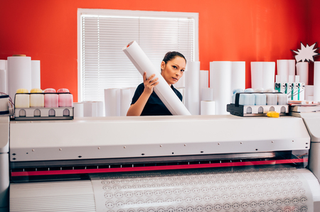 Young woman technician working on plotter and cutter machine in printing centar Banco de Imagens