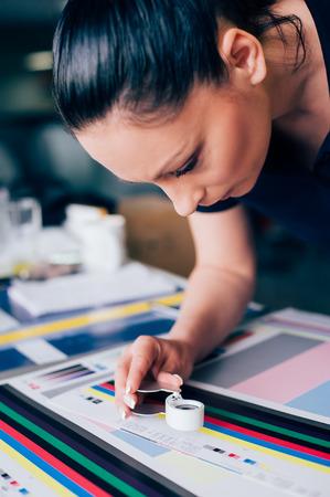 Trabajador en un centro de impresión y prensa utiliza una lupa y comprueba la calidad de impresión Foto de archivo - 78953659
