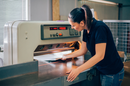 Paper guillotine machine. Worker in a printing and press centar uses industrial knife cutter Stockfoto