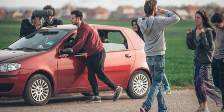 cinematographer: Behind scene improvisation. Film crew team pushing car while cameraman from trunk of car shooting film scene with actor and actress on outdoor location. Group cinema set Stock Photo