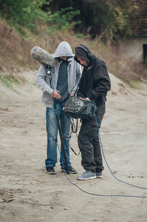 Behind the scene. Sound director and boom microphone operator check equipment on the set before recording