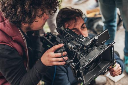 뒤에서. 카메라맨 및 조수가 야외 위치에서 카메라로 필름 장면을 촬영하는 경우 스톡 콘텐츠