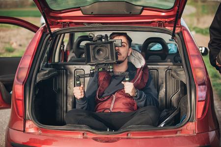 背後にあるシーンの即興。屋外の場所で映画のシーンを撮影の車のトランクからカメラマン