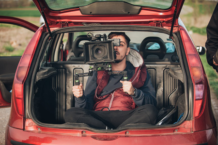 Behind scene improvisation. Cameraman from trunk of car shooting film scene on outdoor location