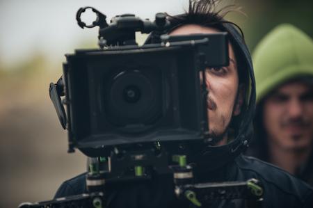 背後にあるシーン。屋外の場所で彼のカメラで映画のシーンを撮影するカメラマン