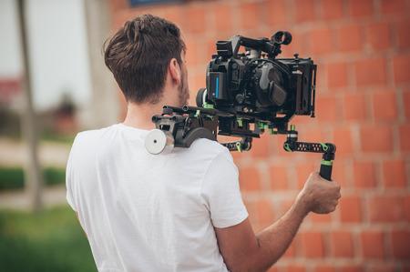 Detrás de la escena. Cameraman disparando la escena de la película con su cámara en la ubicación al aire libre Foto de archivo