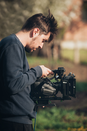high definition television: Behind the scene. Cameraman shooting the film scene with his camera on outdoor location