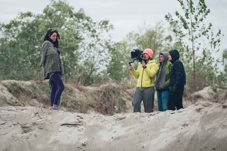 cinematographer: Behind the scene. Actress in front of the camera on the film set outdoor location. Group movie scene