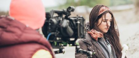 Derrière la scène. Actrice en face de la caméra sur l'emplacement extérieur du film. Scène de film de groupe Banque d'images