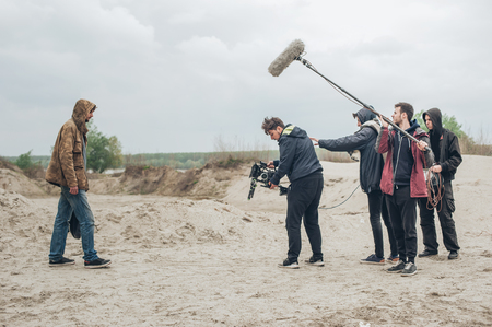 Behind the scene. Film crew team filming movie scene on outdoor location. Group cinema set Reklamní fotografie