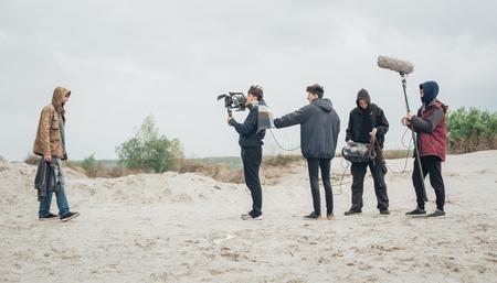 Behind the scene. Film crew team filming movie scene on outdoor location. Group cinema set Foto de archivo