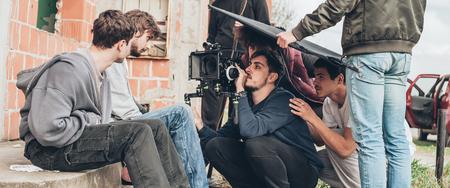 Behind the scene. Film crew team filming movie scene on outdoor location. Group cinema set Standard-Bild