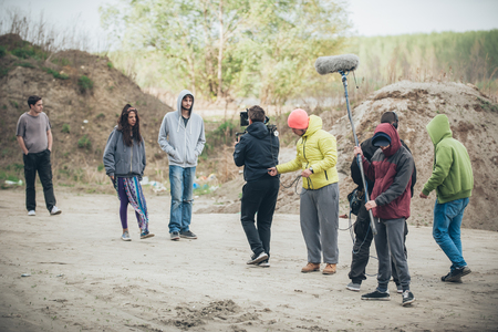 film crew: Behind the scene. Film crew team filming movie scene on outdoor location. Group cinema set Stock Photo