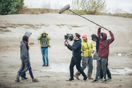 Detrás de la escena. Equipo de la filmación filmando la escena de la película en la ubicación al aire libre. Cine de grupo Foto de archivo