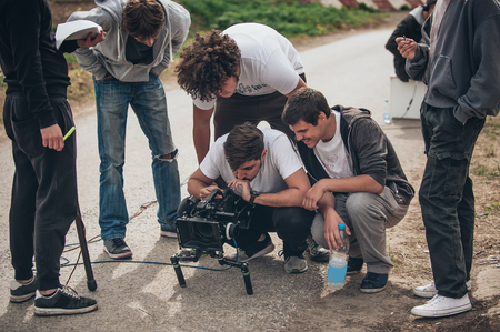 Behind the scene. Film crew team filming movie scene on outdoor location. Group cinema set Stock Photo
