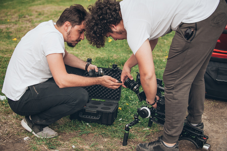 cinematographer: Behind the scene. Cameraman and assistant changes the lens on camera. Outdoor location