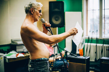 Behind the scene. Famous alternative male singer practice singing on the microphone in the messy recording music studio. Musician live singing