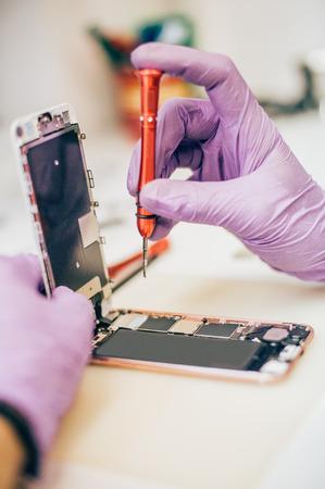 技術者は、電子スマート フォン向け技術サービスで障害のある携帯電話を修復します。携帯電話技術デバイス メンテナンス エンジニア