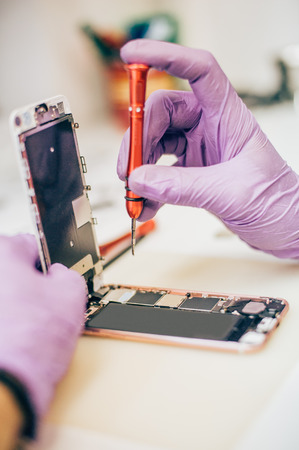 Technician repair faulty mobile phone in electronic smartphone technology service. Cellphone technology device maintenance engineer
