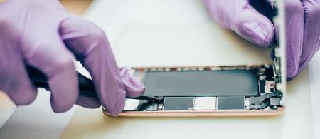 Technicus repareren defecte mobiele telefoon in elektronische smartphone technologie service. Mobiele techniek apparaat onderhoud ingenieur