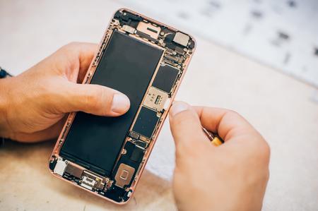 El técnico repara e inserta la tarjeta de memoria sim en el teléfono móvil en el servicio de tecnología electrónica para teléfonos inteligentes. Ingeniero de mantenimiento del dispositivo de tecnología móvil Foto de archivo - 83008849