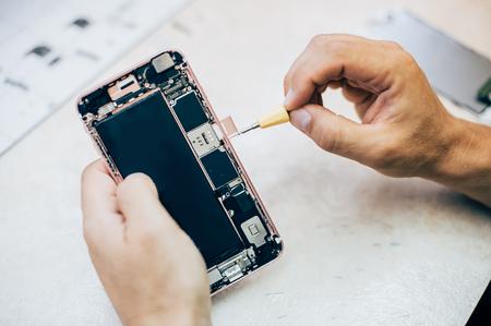 De technicus herstelt en plaatst de sim-geheugenkaart in de mobiele telefoon in de service voor elektronische smartphonetechnologie. Onderhoudstechnicus voor mobiele telefoontechnologie
