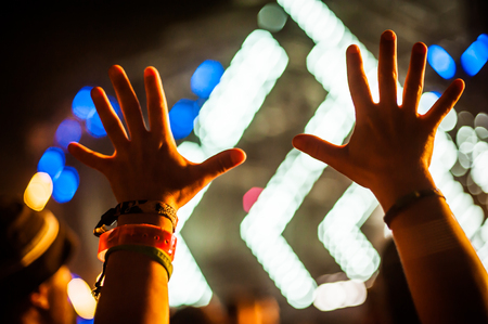Silhouette of raised hands and arms in the air in front of the stage at a concert or a clubbing festival party of electronic music