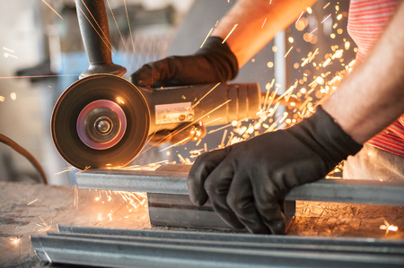 Electric wheel grinding on steel structure in factory. Sparks from the grinding wheel