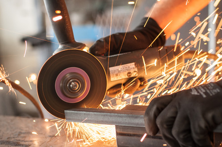 flying disc: Electric wheel grinding on steel structure in factory. Sparks from the grinding wheel