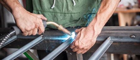 Industrial worker welding the steel structure in the workshop. Flies of spark from hot metal Stock Photo