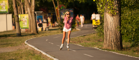 BELGRADE, SERBIA - 03. JULY 2011. Unidentified beautiful girl talk phone and drives roller skate around the Ada Ciganlija lake in the Belgrade, capital of Serbia. Belgrade known for beautiful girls