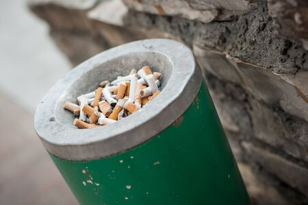 The dirty ashtray is full of cigarettes butt and ashes. Real life scene