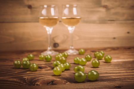 Two glasses of white wine and grapes on wooden table. Close up
