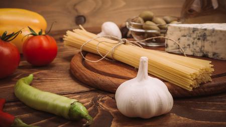 Food ingredients for preparing pasta on wooden kitchen board. Vegetables, sauces