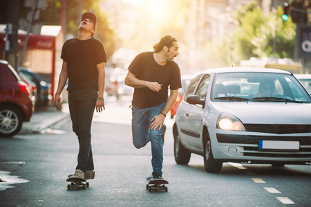 skateboarder: Two pro skateboard rider ride skate in front of the car on the city road street through traffic jam Stock Photo