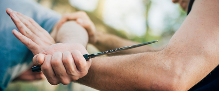 Kapap 강사는 위협 및 칼 공격에 대하여 무술 자기 방위 칼 공격 무장 기술을 설명합니다. 무기 유지 및 무장 해제 진짜 금속 칼로 데모하기 스톡 콘텐츠