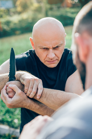 Kapap instructor demonstrates martial arts self defense knife attack disarming technique against threat and knife attack. Weapon retention and disarm training. Demonstration with a real metal knife