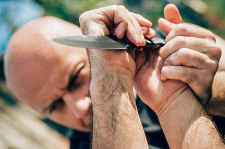 El instructor de Kapap demuestra la técnica de desarme de ataque de cuchillo de defensa de artes marciales contra ataque de cuchillo y amenaza. Retención de armas y entrenamiento de desarme. Demostración con un cuchillo de metal real