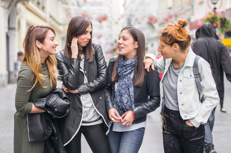 Four girls friends, gossip and having fun on the street. Close up