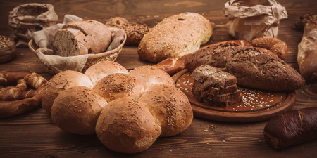 Various baked breads and rolls on rustic wooden table. Close up