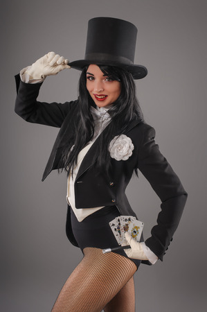 Pretty female magician dressed in performer costume suit with magic wand and playing cards. Studio shoot Foto de archivo