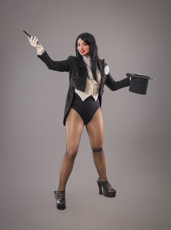 Beautiful female magician dressed in costume suit with magic stick doing trick. Studio shoot