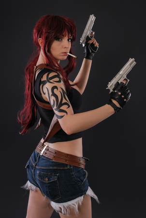 Portrait of beautiful sexy woman with two gun on black background Stock Photo