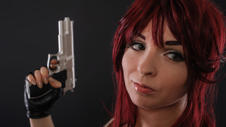 Beautiful redhead woman with gun against dark background. Close up