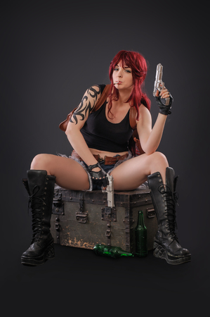 Portrait of sexy woman posing in studio with gun. Against a black background