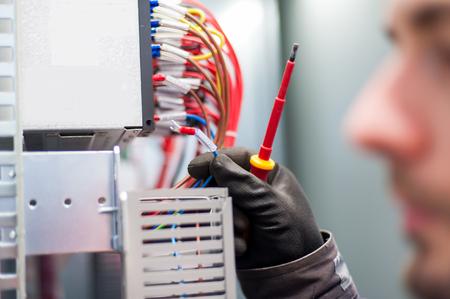 De close-up van elektricieningenieur werkt met elektrische kabeldraden van de doos van de zekeringsschakelaar. Elektrische apparatuur