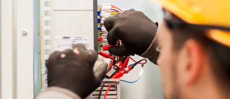 Closeup of electrician engineer works with electric cable wires of fuse switch box. Electrical equipment