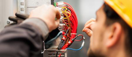 Engenheiro eletricista testa instalações elétricas e fios no sistema de proteção de revezamento. Unidade de controle da baía. Aparelhagem de Média Tensão Foto de archivo - 94191379