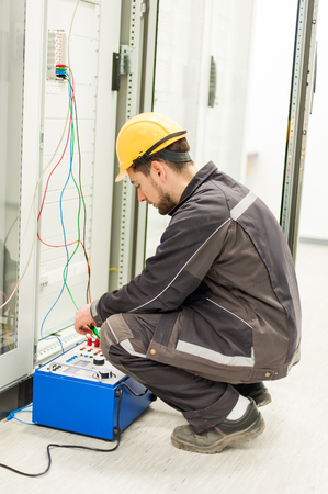 Electrician engineer tests system with relay test set equipment. Relay and protection testing