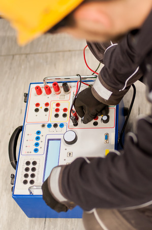 Maintenance engineer inspect system with relay test set equipment. Relay and protection testing